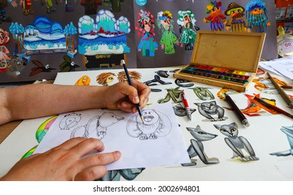 The animator draws with a pencil and draws characters from cartoons, comics or puppet shows. Preparing to make a doll. The designer creates sketches. Comics, cartoons, puppet theater