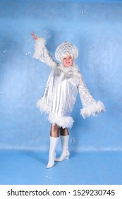 Animator woman in the Studio on a blue background in a snow maiden costume and clown outfit flaunts for the audience