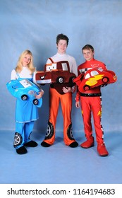 Animators dressed as Sally Lightning McQueen and mater tractor on blue background