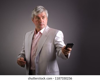 Animposing respectable grey-haired man. A handsome imposing respectable grey-haired man wearing a light-colored jacketis holding a mobile phone.