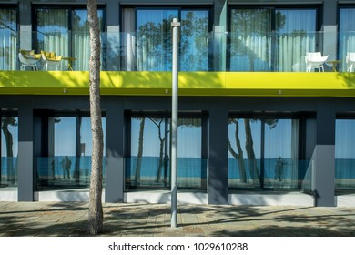 an anise green building with reflections of the seashores in the windows