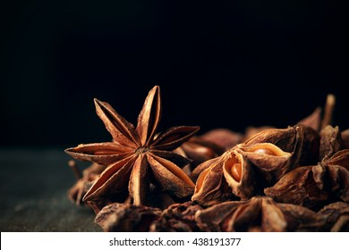 Anise star seeds on the wooden background. Aromatic ingredient in culinary, raw for alcohol drink arak, ouzo, raki, sambuca. Macro, close-up. Selective Focus. Toned image.