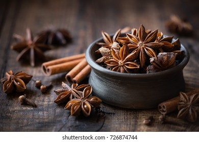 Anise stars in a black bowl with cinnamon sticks and cloves. Winter seasonal baking concept with copy space for your text