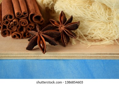 Anise stars, cinnamon sticks and kataifi dough on the wooden board against the blue background