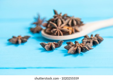 Anise in a wooden spoon on a blue table