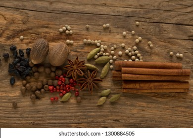 Aniseed (anise seed), barberry, cardamom, red pepper, white pepper, nutmegs, and cinnamon sticks on the wooden surface (background) of the kitchen table among the spices