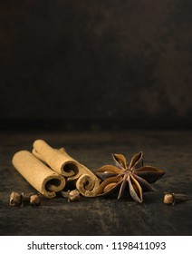 Aniseed star, cinnamon sticks and cloves on a rustic background with copy space for your text