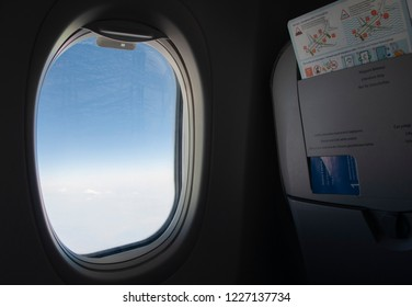 """Ankara, Turkey - 08/26/2018: Airplane pothole with a sky view. A seat with an evacuation plan and the text """"Fasten seat belt while seating, literature only, life..."""""""