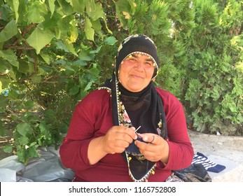 Ankara, Turkey / August 17th 2018: Traditional Turkish woman with beautiful, peaceful face and decorated head covering doing handicraft and selling her products to visitors