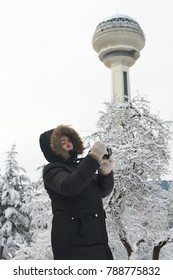 ANKARA, TURKEY - DECEMBER 25, 2017:  A woman takes photo in front of Atakule in a snowy morning. Atakule is one one of the primary landmarks of Ankara. - Turkey