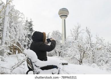 ANKARA, TURKEY - DECEMBER 25, 2017: A woman takes photo in Botanic Park in the snow. Botanic Park and Atakule are among the main attraction points of Ankara. - Turkey