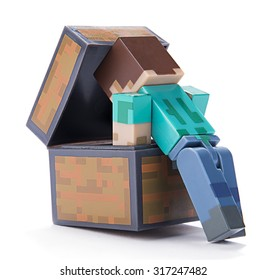 Ankara, Turkey  July 01, 2015: Minecraft figure Herobrine checking inside of a chest isolated on white background.  Minecraft is a game about breaking and placing blocks.