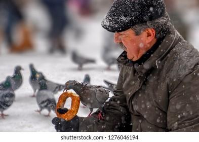 Ankara/Turkey-December 06 2018: Man feeding pigeon on his hand with simit which is Turkish bagel