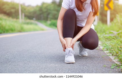Ankle injury and pain from jogging. Young fitness man holding his sports leg injury after running and exercise outside in summer