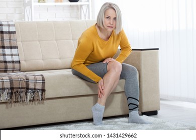 Ankle pain, painful point. Unhappy woman suffering from pain in leg at home. Physical injury concept.