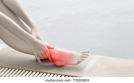 ankle pain in women, young Woman massaging her ankle beside pool