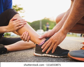 Ankle sprained. Young woman suffering from an ankle injury while exercising and running and she getting help from man touching her ankle. Healthcare and sport concept.