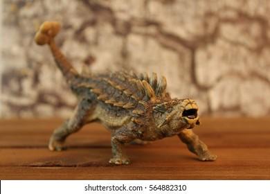 Ankylosaurus dinosaur toy with rock background.