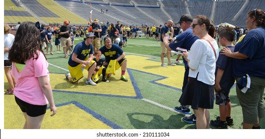 ANN ARBOR, MI - AUGUST 10:  University of Michigan football fans take photographs at mid-field at Michigan Football Youth Day on August 10, 2014 in Ann Arbor, MI.