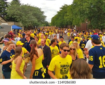 ANN ARBOR, MI - AUGUST 31, 2013: Sea of University of Michigan Wolverine fans crowd the streets heading to Michigan Stadium. Michigan routinely sells out football games with over 100,000 attendees