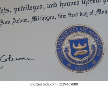 ANN ARBOR, MI – JUL 28 2018: Closeup of a diploma of the University of Michigan issued in 2014 showing embossed seal, text, and signature of president Mary Sue Coleman