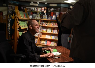 """ANN ARBOR, MI - JUNE 25: New York Times bestselling author Jim Ottaviani places his thumbprint on a book at a signing for his new book """"Primates"""" at Nicola's Books June 25, 2013 in Ann Arbor, MI."""