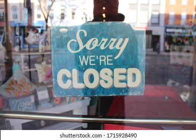 Ann Arbor, Michigan / United States - April 26 2020: wooden blue and white closed sign sorry we're closed antique sign coronavirus covid-19 outbreak downtown Ann Arbor Governor Gretchen Whitmer