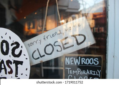 Ann Arbor, Michigan / United States - April 26 2020: Sorry we're closed wooden closing sign covid-19 downtown Ann Arbor 2020 Governor Gretchen Whitmer extends stay at home order Michigan coronavirus