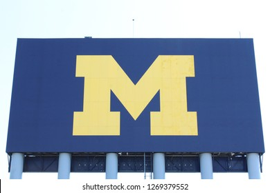 "Ann Arbor, MI/USA: July 13, 2018 – Sign with iconic maize and blue ""Block M"" logo of University of Michigan in Ann Arbor Michigan outside its football stadium, affectionately known as The Big House."