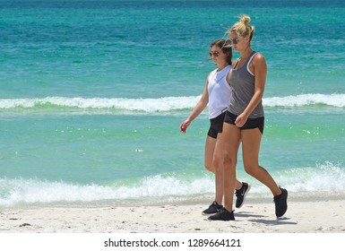 ANNA MARIA ISLAND, FL / USA - April 29, 2018: Two Young Women on vacation taking a leisure walk and enjoying the beach.