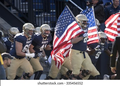 ANNAPOLIS, MD - OCTOBER 31: The Navy football team runs onto the field carrying American flags prior to the AAC football game October 31, 2015 in Annapolis, MD.