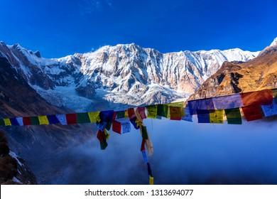 ANNAPURNA BASE CAMP, NEPAL - DEC 1, 2018: Morning view of Mount Annapurna I from Annapurna base camp with prayers flags, round Annapurna circuit trekking trail, Nepal.