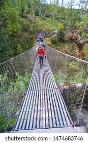 Annapurna Basecamp, Nepal - April 10, 2018: Nepali porter with heavy load crossing crossing suspension bridge.