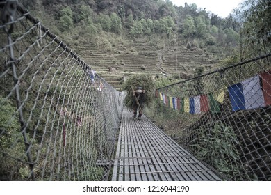 Annapurna Basecamp Nepal ,April 16, 2018:Nepalese An old man boldly carries a large bunch of grass crossing a suspension bridge