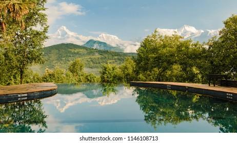 Annapurna mountain range reflecting in an infinity pool in a resort, Pokhara, Nepal.