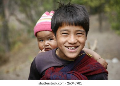 ANNAPURNA, NEPAL  - MARCH 19 : A young boy carries his baby sister while teasing trekkers for food on March 19, 2008 in Annapurna, Nepal. Annapurna region is well known for its trekking activities.