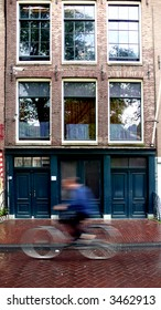 anne franks house in amsterdam while a cyclist is going by in front of it