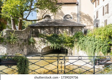ANNECY, FRANCE - 28 SEPTEMBER 2019: picturesque canal house at the rear of the Cathedral. Framed by lush bushes and trees.