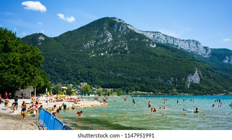 Annecy France, 30 July 2018: People enjoying the sunny summer day at Albigny beach and swimming in Annecy lake with Alps mountains in background in France