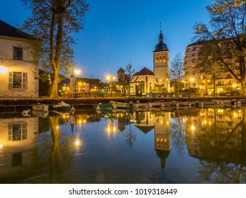 ANNECY, FRANCE - APRIL 13 : Tower and building of church of St.Maurice, near canal in Annecy, France, under evening twilight sky on April 13, 2017.