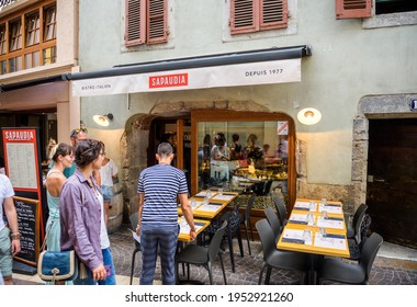Annecy, France - Aug 15, 2017: Worker waiter owner of resturnat preparing the outdoor terraced tables of Sapaudia Bistro Italien in city center - custoemrs walking in front