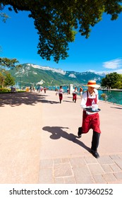 Annecy, France - August 25, 2010: An apron wearing waiter runs with a loaded tray around Annecy Lake at the French Alps during the Waiter's Race Run