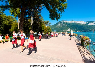 Annecy, France - August 25, 2010: Many waiters wearing red aprons running with loaded trays around Annecy Lake at the French Alps during the Waiter's Race