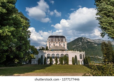 Annecy, France - August 8, 2018. Side view of Imperial Palace hotel on shore of Lake Annecy in Haute-Savoie, Rhone-Alpes region. Belle Epoque building in French Alpes with mountains background.