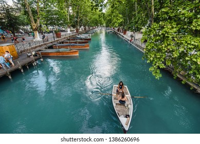 Annecy, France - August 8, 2018. View of Thiou River with boating people and wooden sailboats from Lover's bridge -popular touristic landmark and attraction place. Promenade in medieval french town.