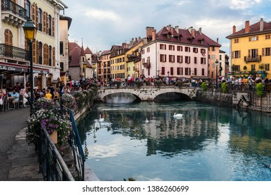 Annecy, France - August 8, 2018. View of french medieval Annecy old town with colorful building facades, touristic cafes, restaurants and stone bridge through Thiou River with white swans and flowers.