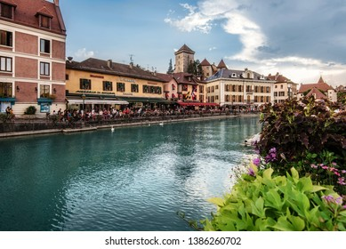 Annecy, France - August 8, 2018. View of french medieval Annecy old town with colorful building facades, touristic cafes, restaurants and Thiou River promenade with flowers on riverbank.