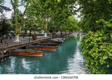 Annecy, France - august 8, 2018. View of Thiou River with wooden sailboats from Lover's bridge Pont des Amours - popular touristic attraction place. River promenade in medieval french town.