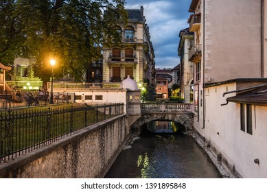 Annecy, France - August 8, 2018. View of french Annecy old town with Thiou river canal, medieval building facades, stone bridges, evening illumination, lightening lampposts and trees, without people.