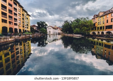 Annecy, France - August 8, 2018. View of french medieval Annecy old town and Thiou river canal with sky and residential building reflections in water. French prealpine city popular observation deck.